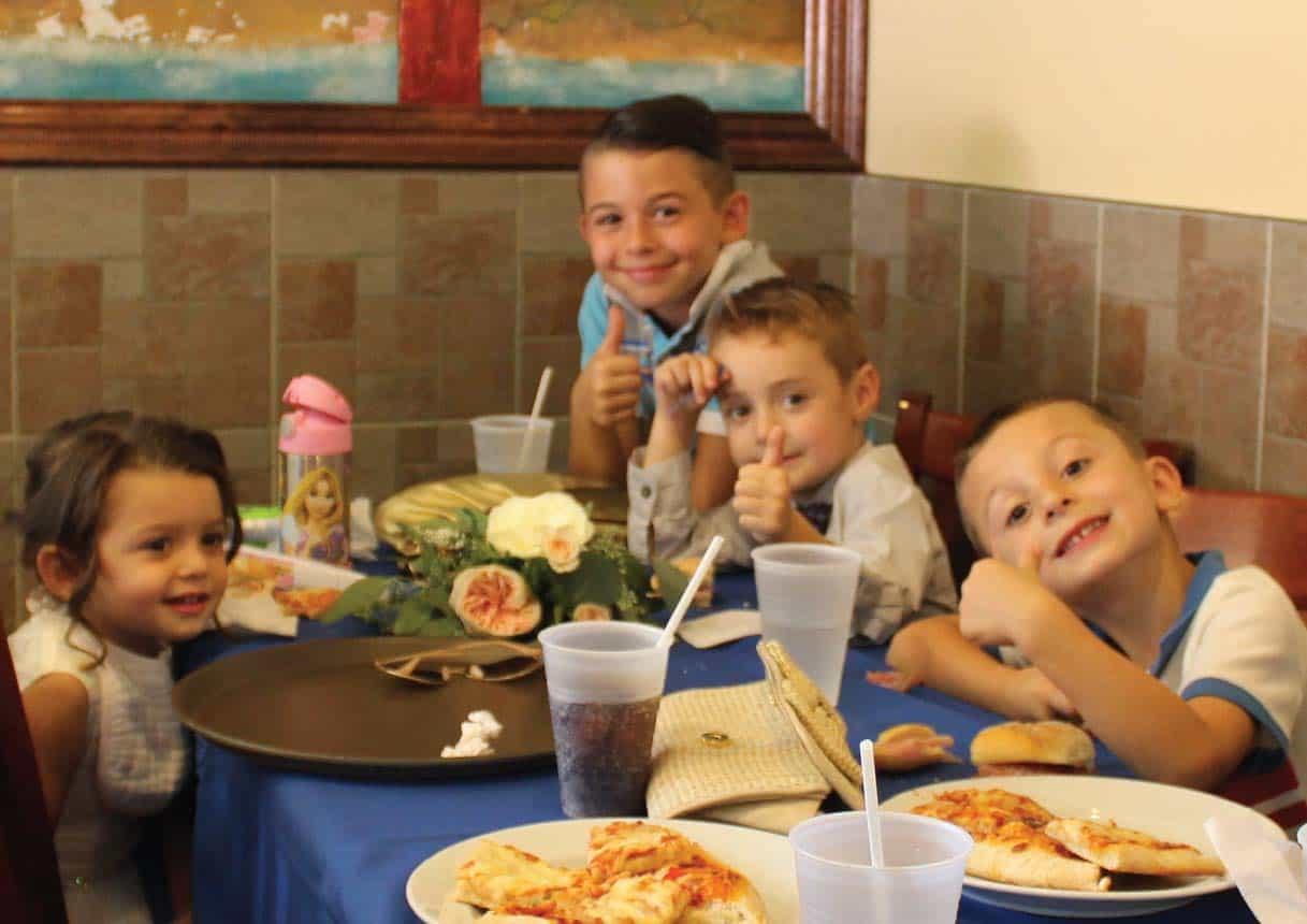 KIDS ENJOYING BIG SLICE ITALIAN FOOD
