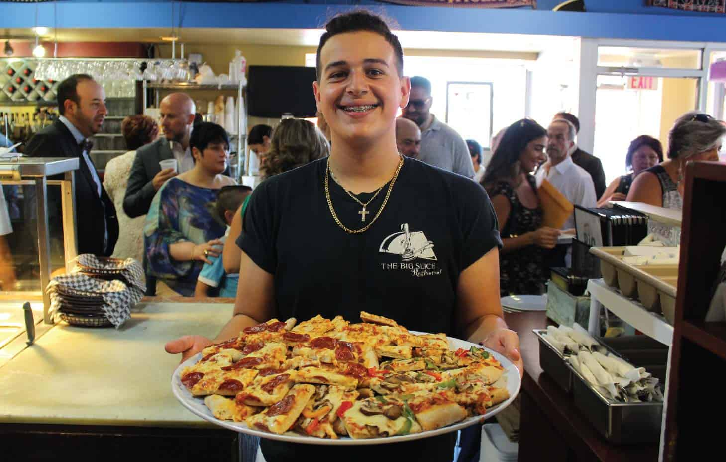 PICTURE OF YOUNG SALVATORE LUCIANNO, GRANDSON OF GIUSEPPE, HOLDING A TRAY OF PIZZA