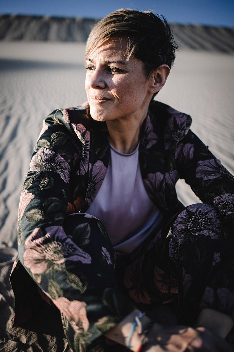 Diana sitzend in der Wüste, lächelt und denkt nach
