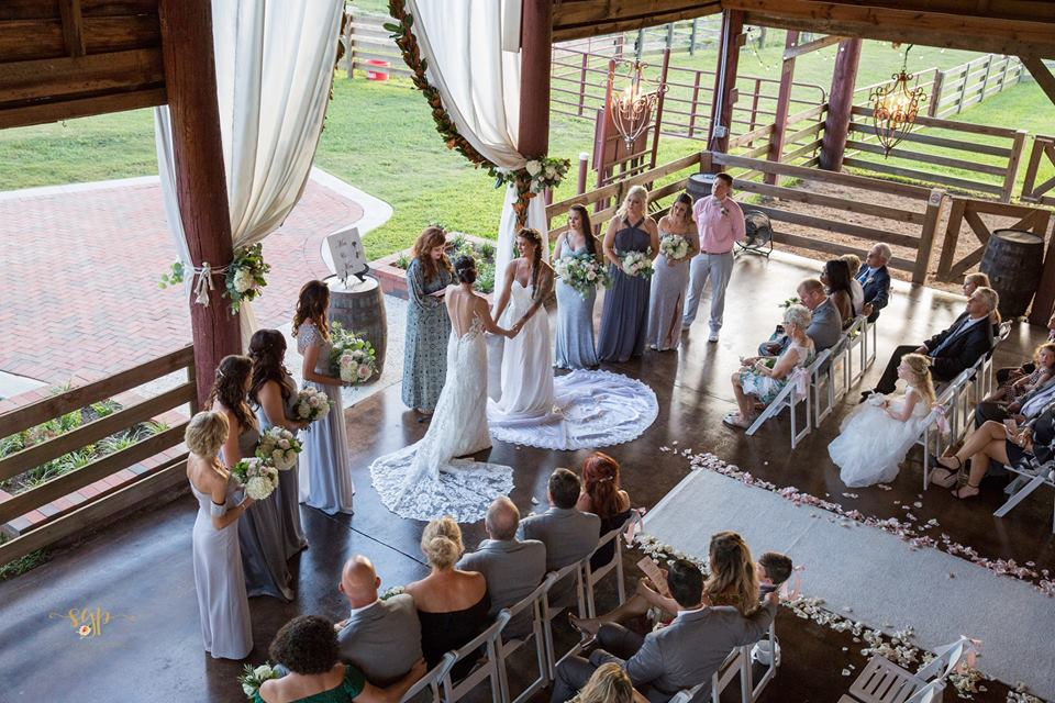 barn style wedding for two women standing before a seated crowd holding hands, taking their vows