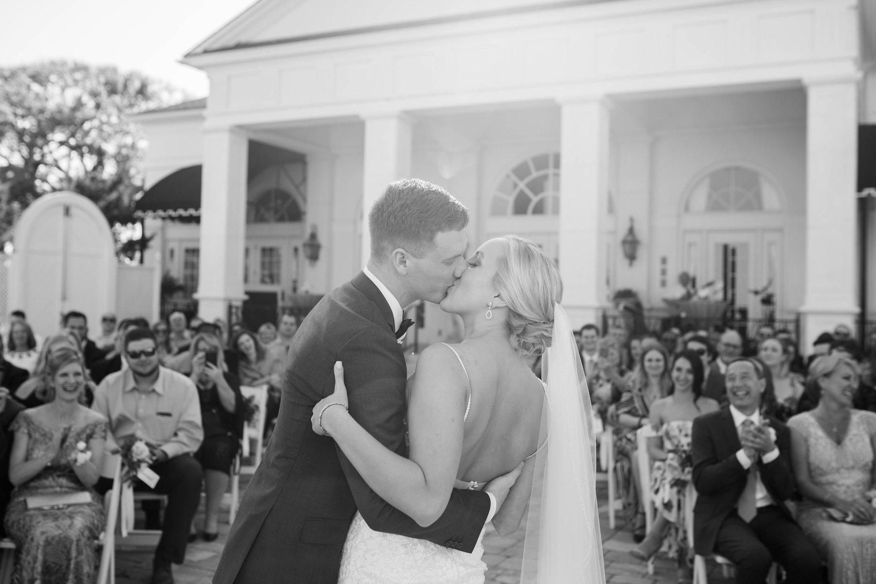 black and white photo of a newlywed couple kissing at the end of their ceremony with a clapping crowd seated in the background