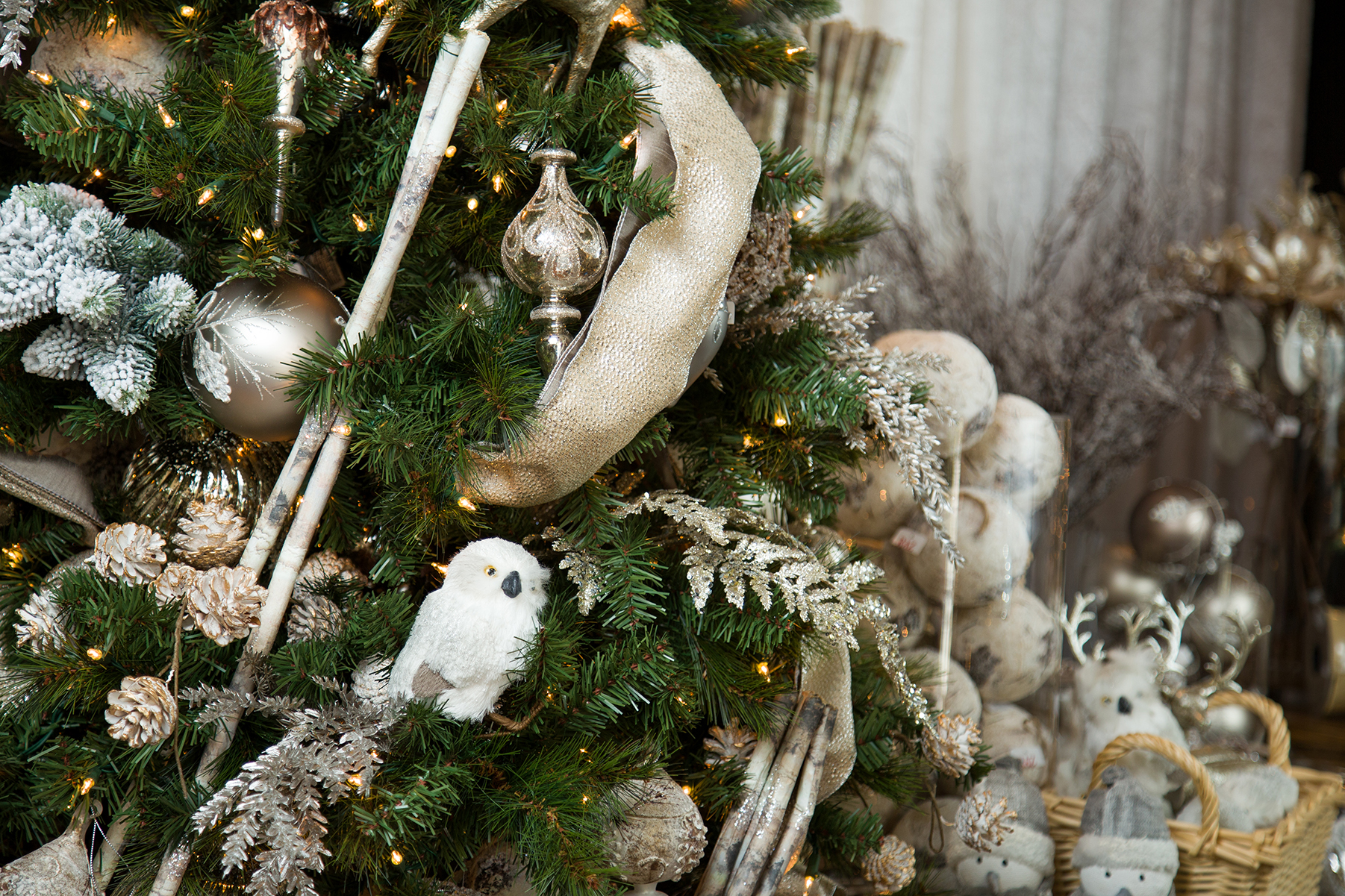 closeup of a Christmas tree adorned with Ivory, gold and silver ornaments with a decorated table on the bottom left behind the tree