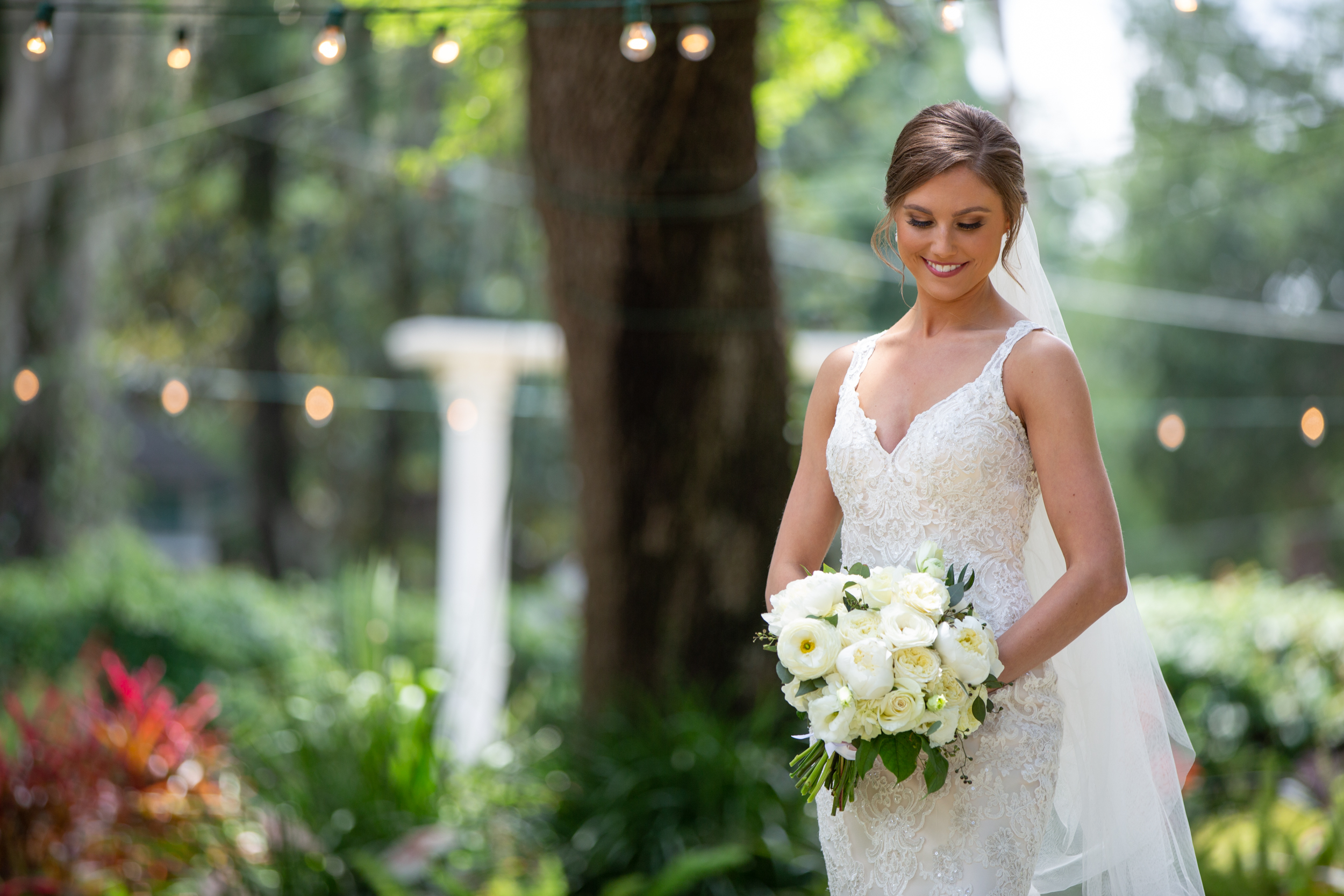 a bride in white smiling as she looks down at her bouquet on a sunny day