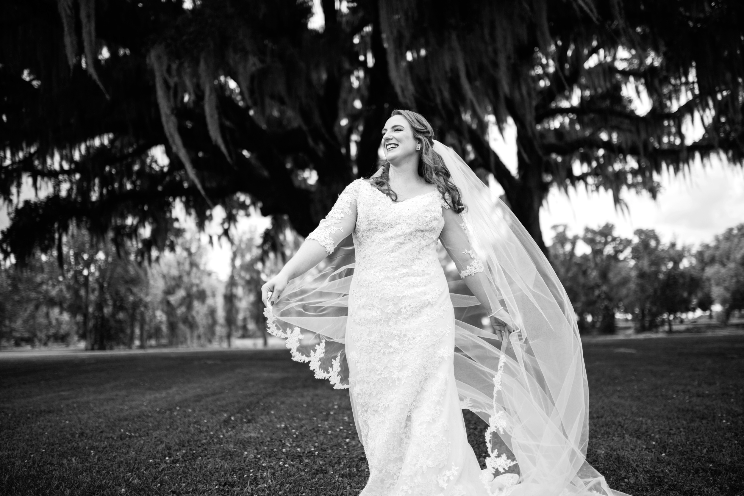 black and white photo of a bride standing outdoors with the wind blowing her veil
