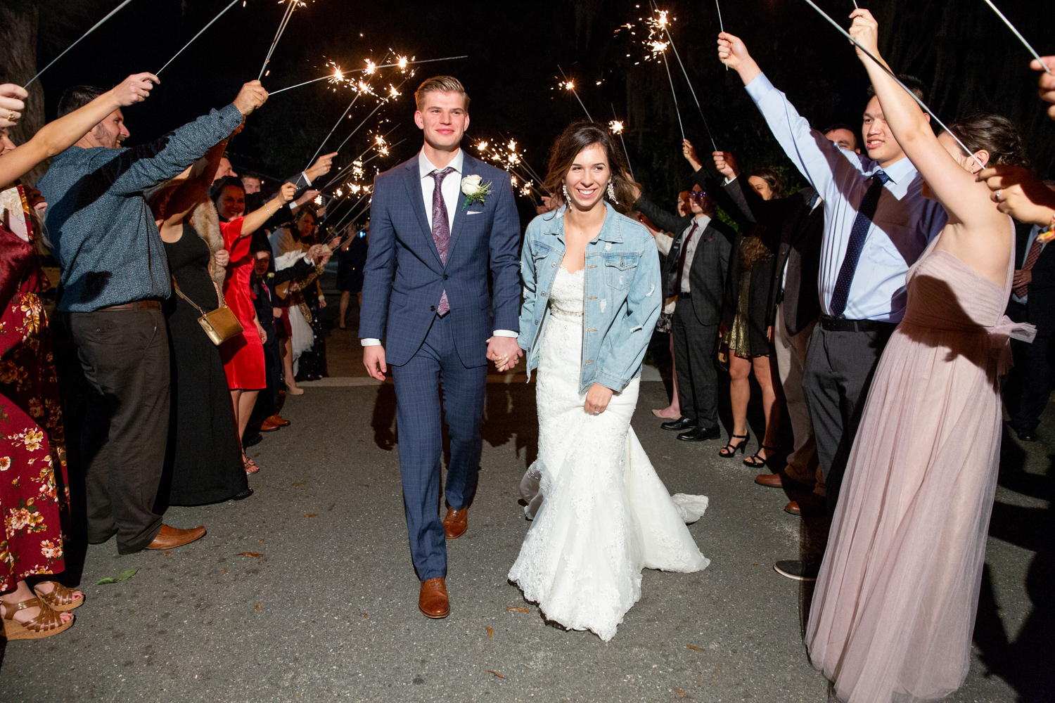 a young couple at their reception walking between  2 rows of guests holding sparklers aloft