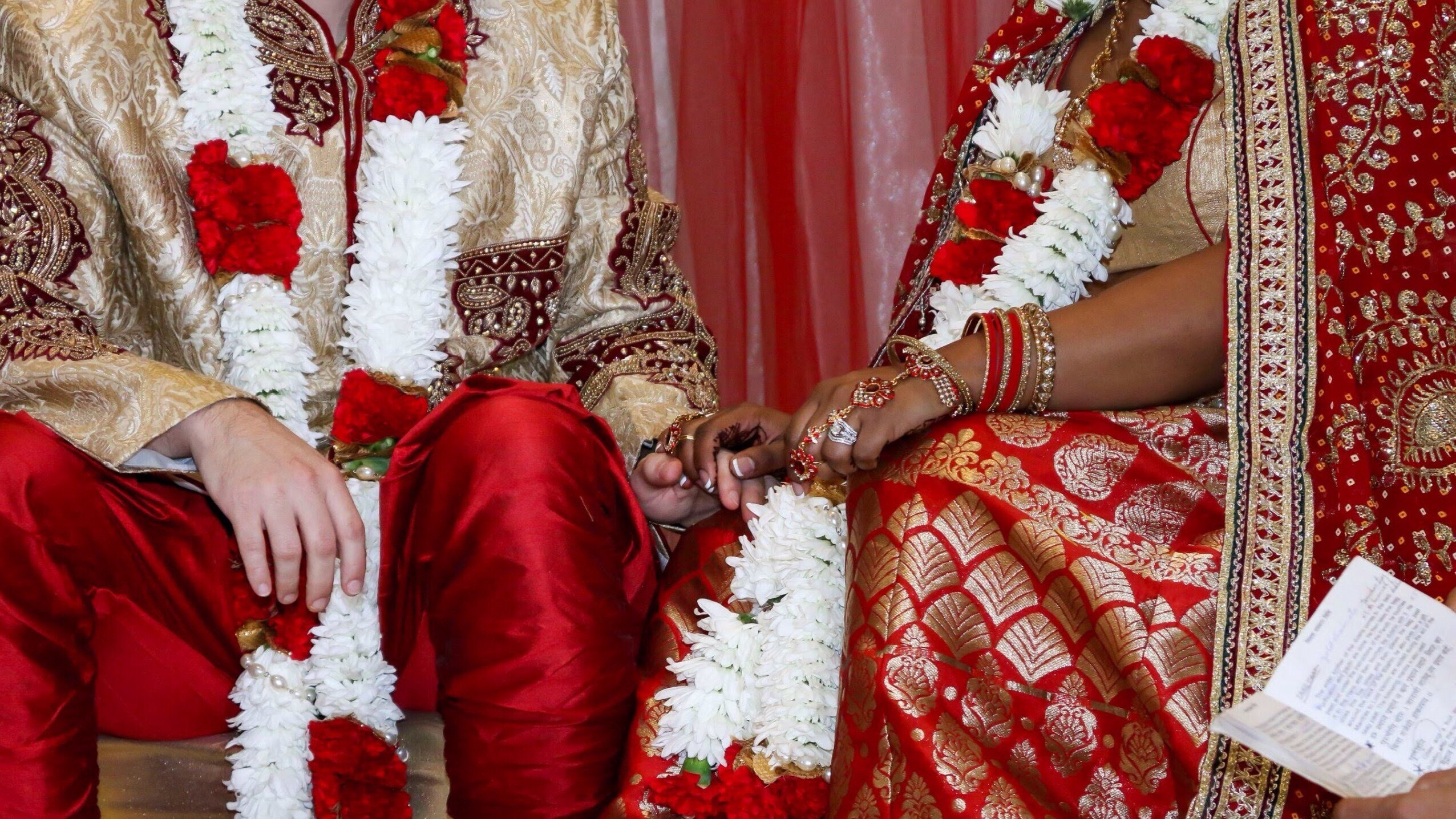 close up photo of a couples hands and legs wearing traditional East Indian wedding attire adorned with flowers, the clothing and flowers are all bright red, white and gold