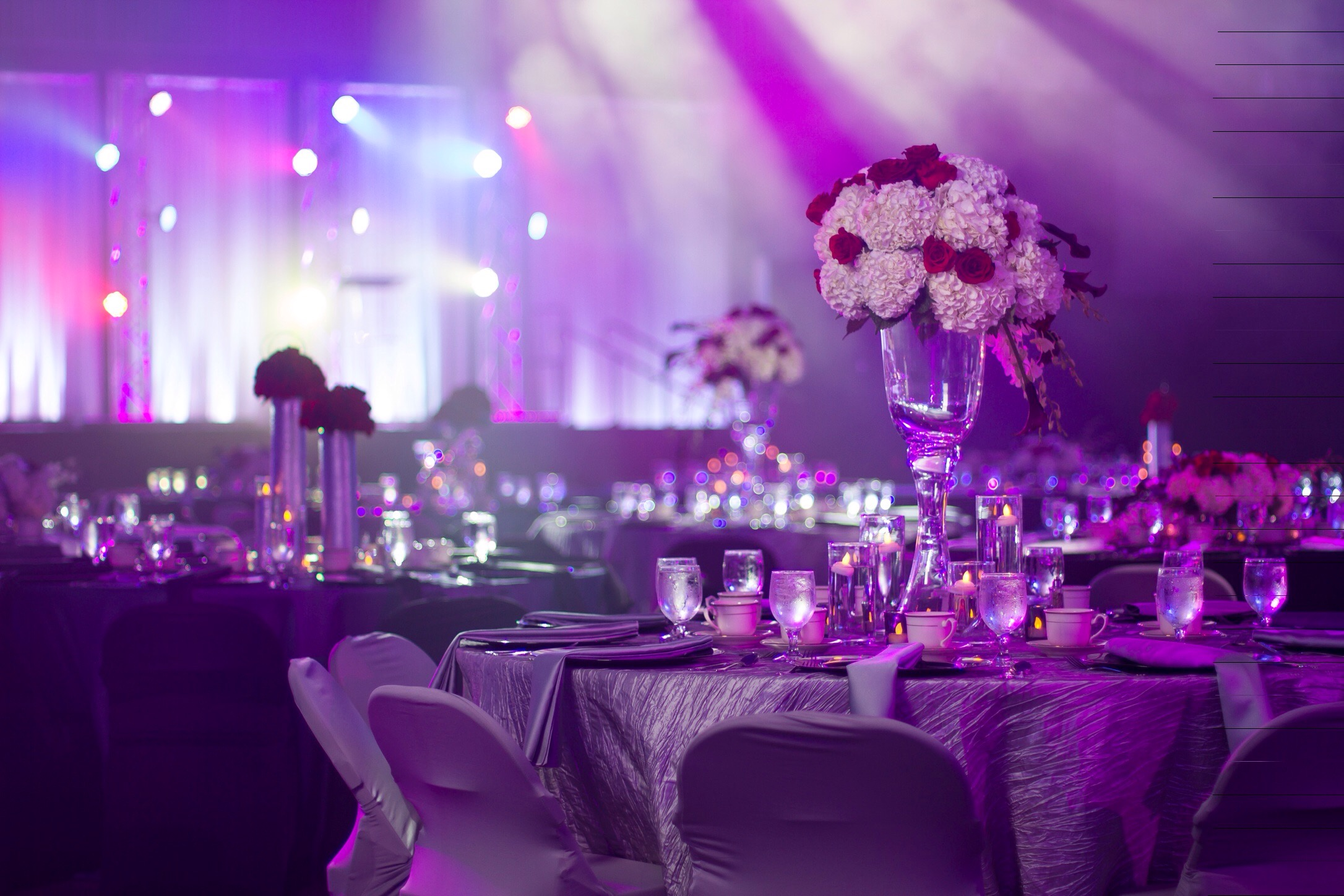 Purple and white light bathe an elegant dining area full of tables with large floral centerpieces