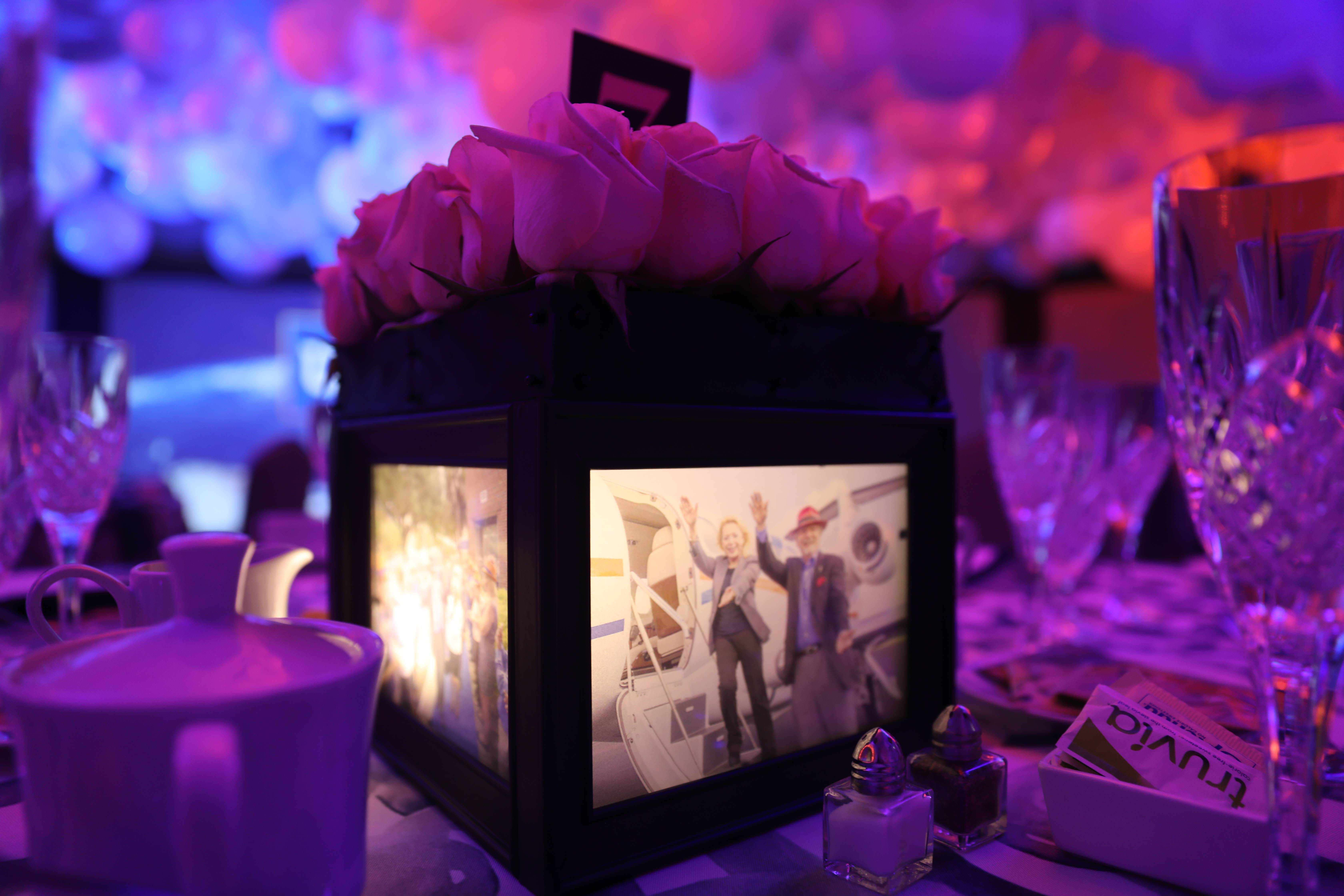Close-up image of a lit picture box on a table set for 8 with purple lighting washing the room, the box is topped with a dozen cut roses.