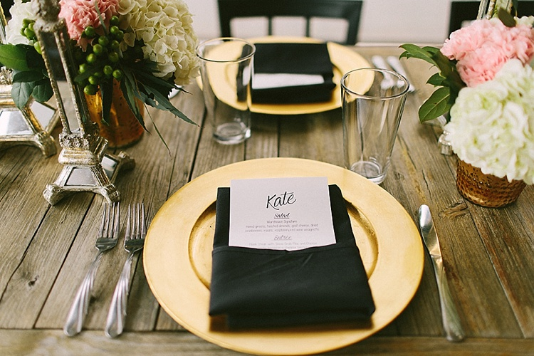a dark wooden table with gold charger plate, silverware, a black napkin folded in a wide rectangle with a place holder containing a guests name