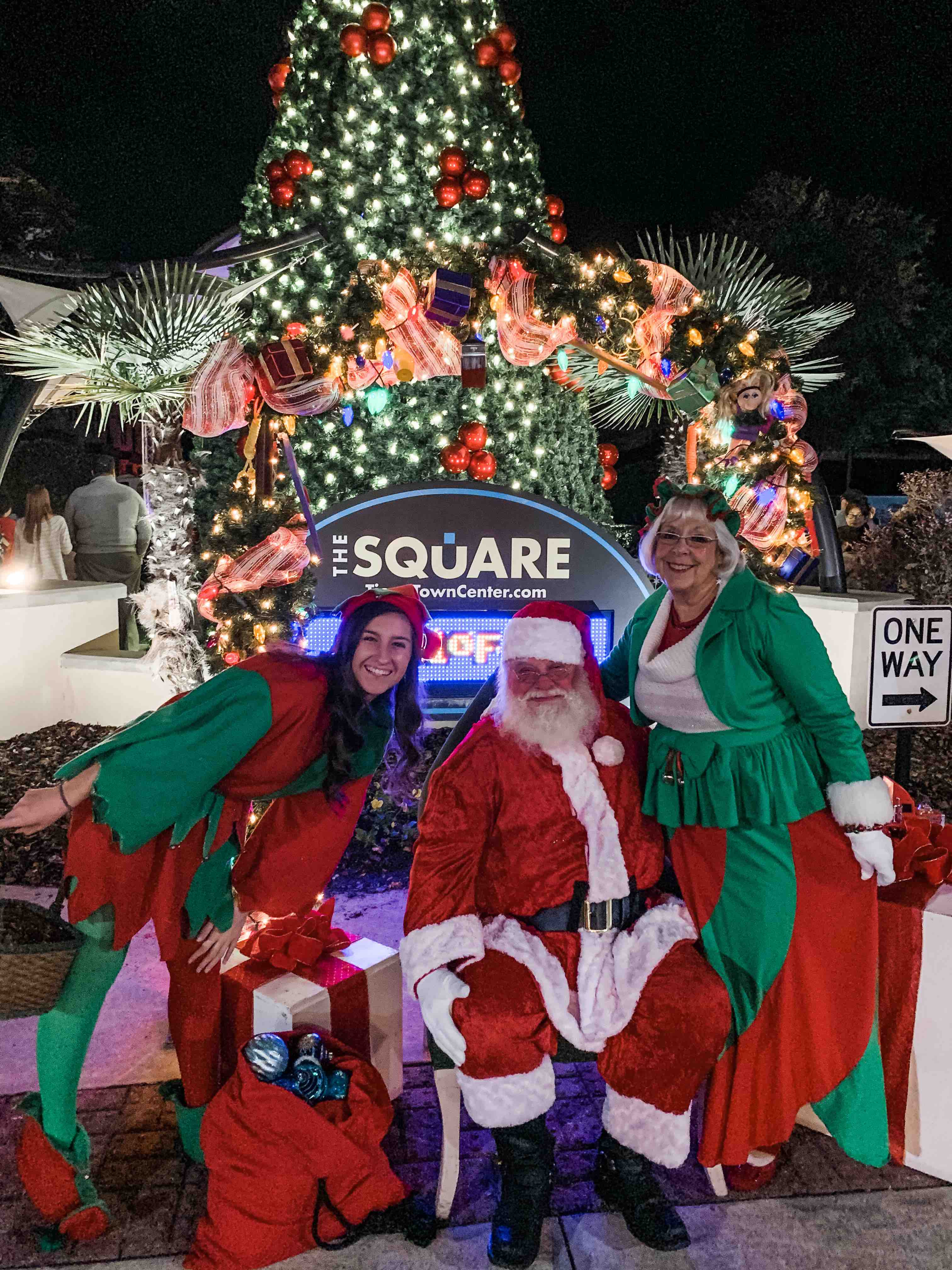 Santa Clause look a like and helpers in front of a Christmas Tree at night in Tioga Town Center