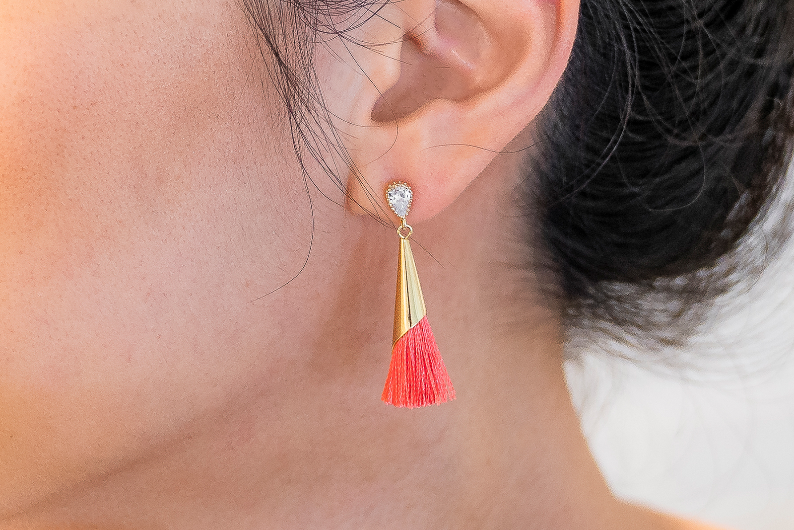 close up of Hello Prosper coral teardrop earrings