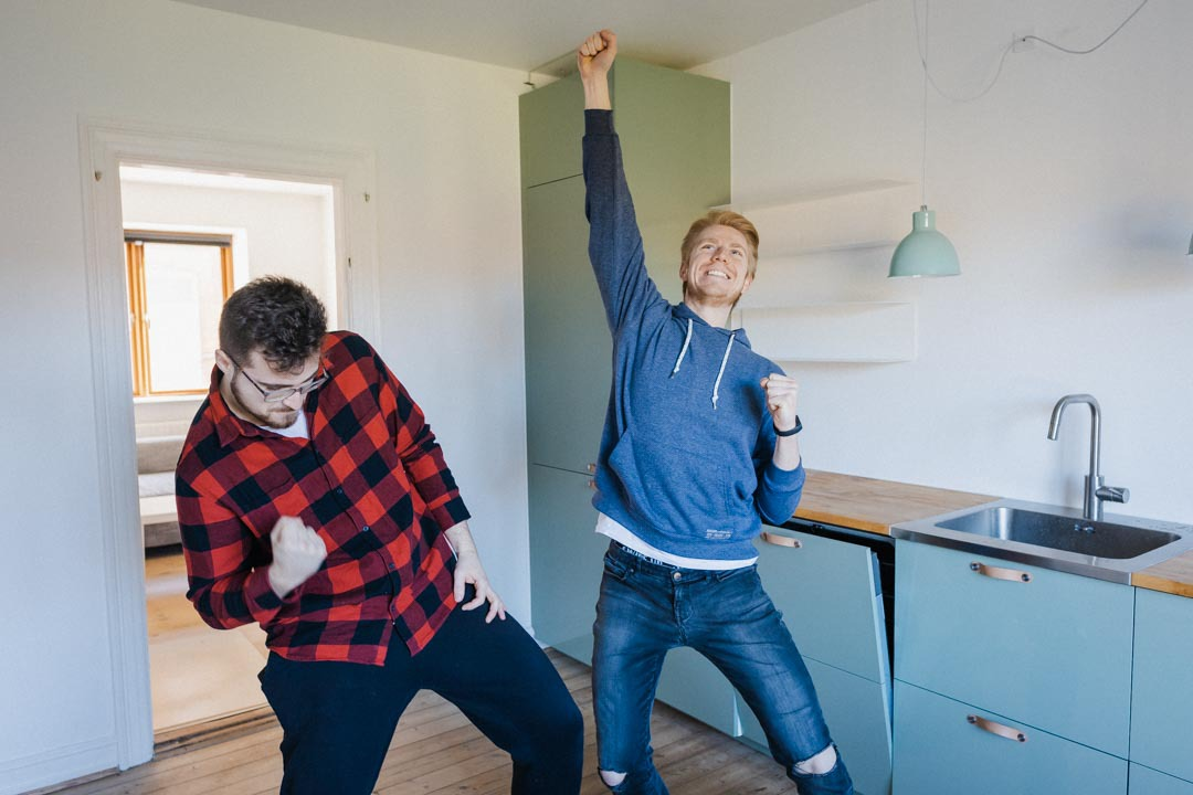 Two students in their new kitchen, looking happy.