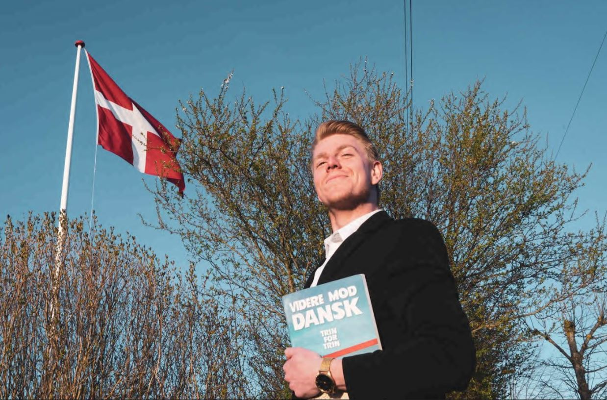 Proud student holding a Danish textbook. Danish flag visible in the back.in