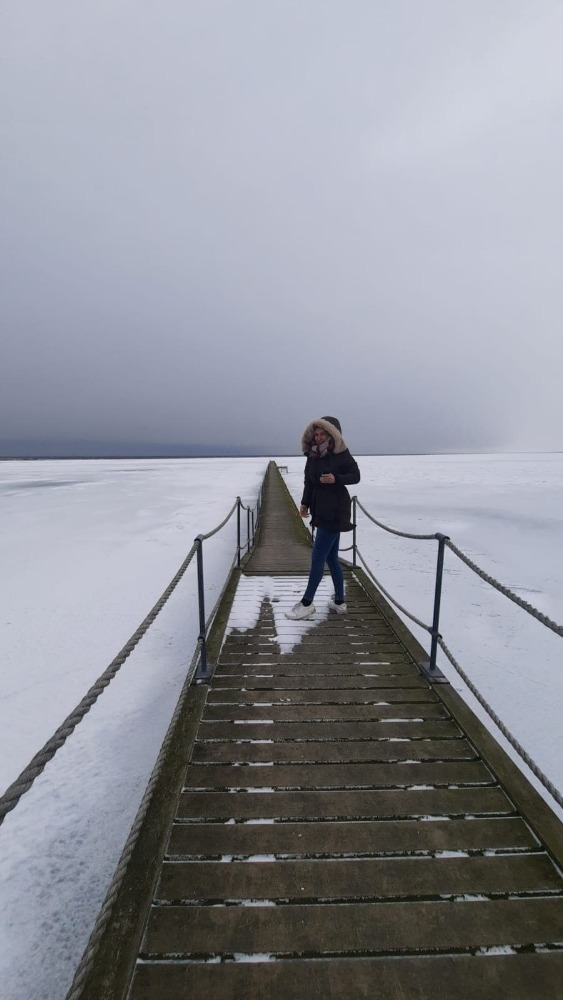 Young woman standing on a dock while the water is frozen around her