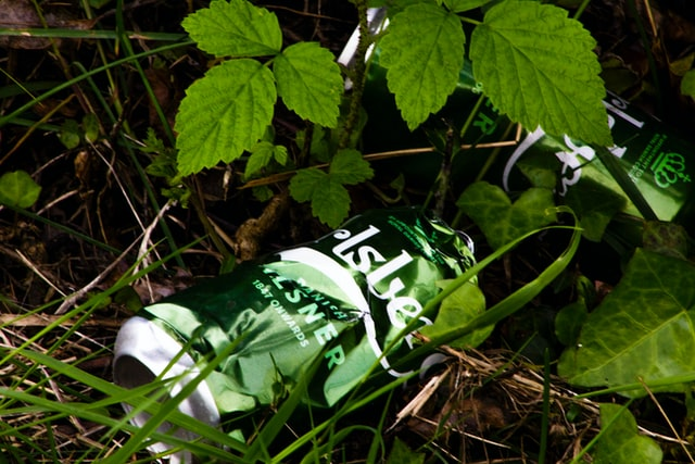 empty beer dose thrown out in the grass