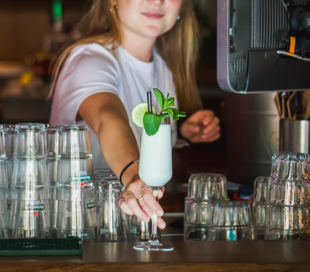 Young female student working as a bartender