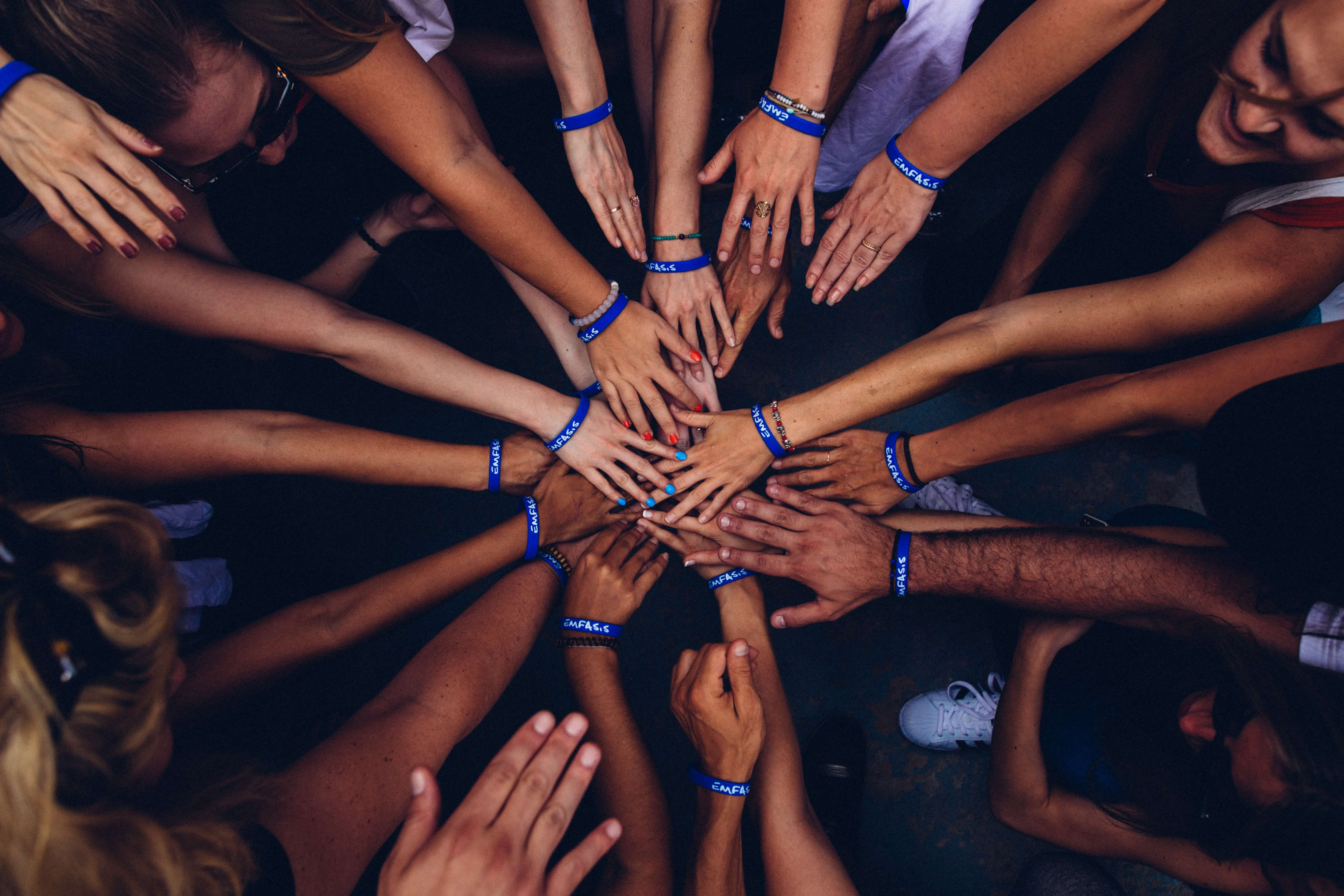 Diverse set of people all putting hands together, united.