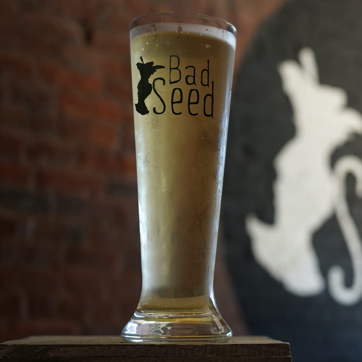 A tall glass full of Bad Seed's flagship hard cider sitting on a rustic wooden plank with a brick wall in the background.