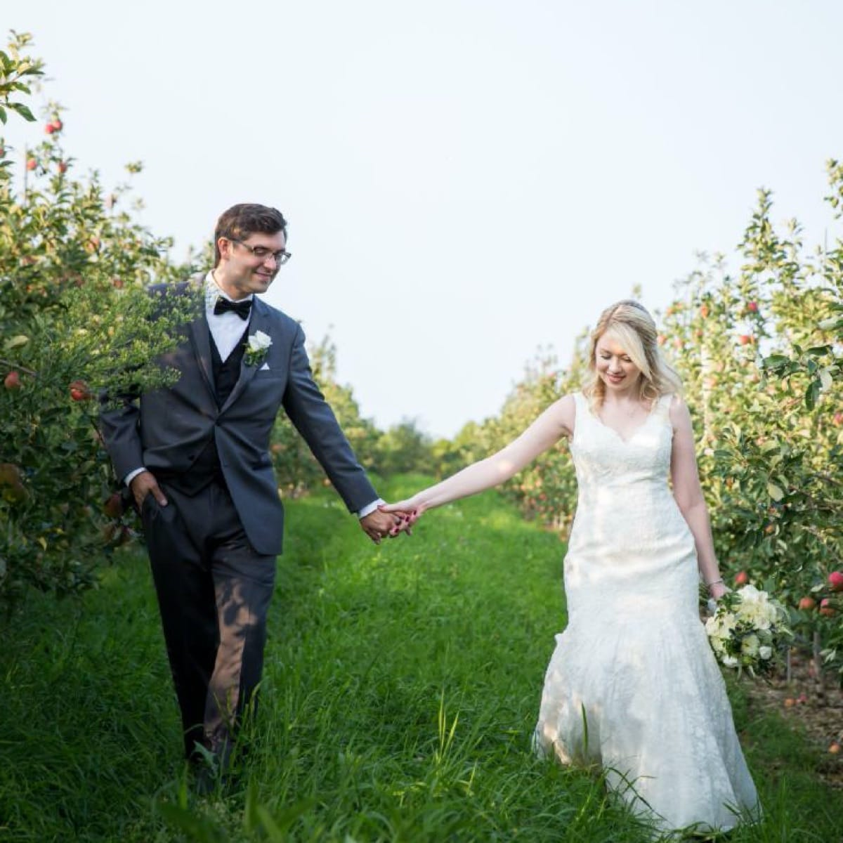 Newlywed couple holding hands and walking through an apple orchard.