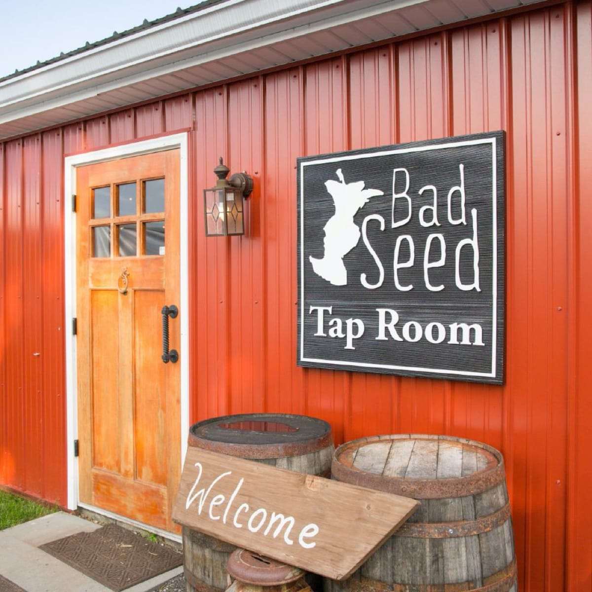 A wooden door and red barn siding with a welcome sign showing the entrance to the Bad Seed Tap Room.