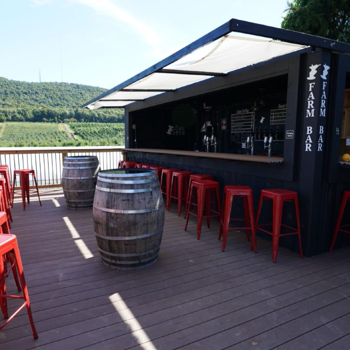 Two wooden barrels and a collection of red bar stools on the outdoor patio at the Bad Seed Farm Bar.