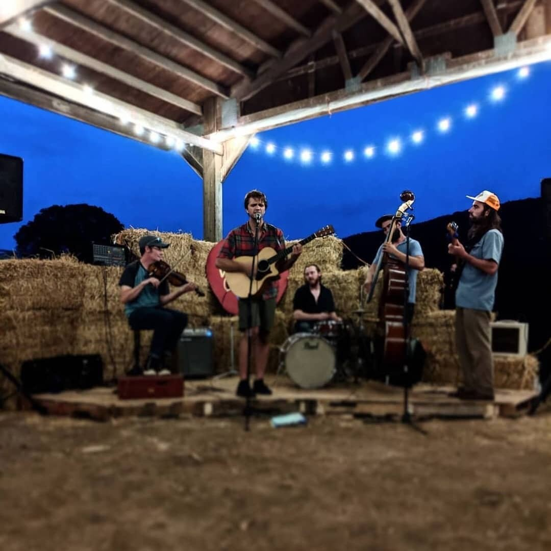 Bluegrass band playing outside against stacks of hay for Bad Seed's Farmside Friday Nights series