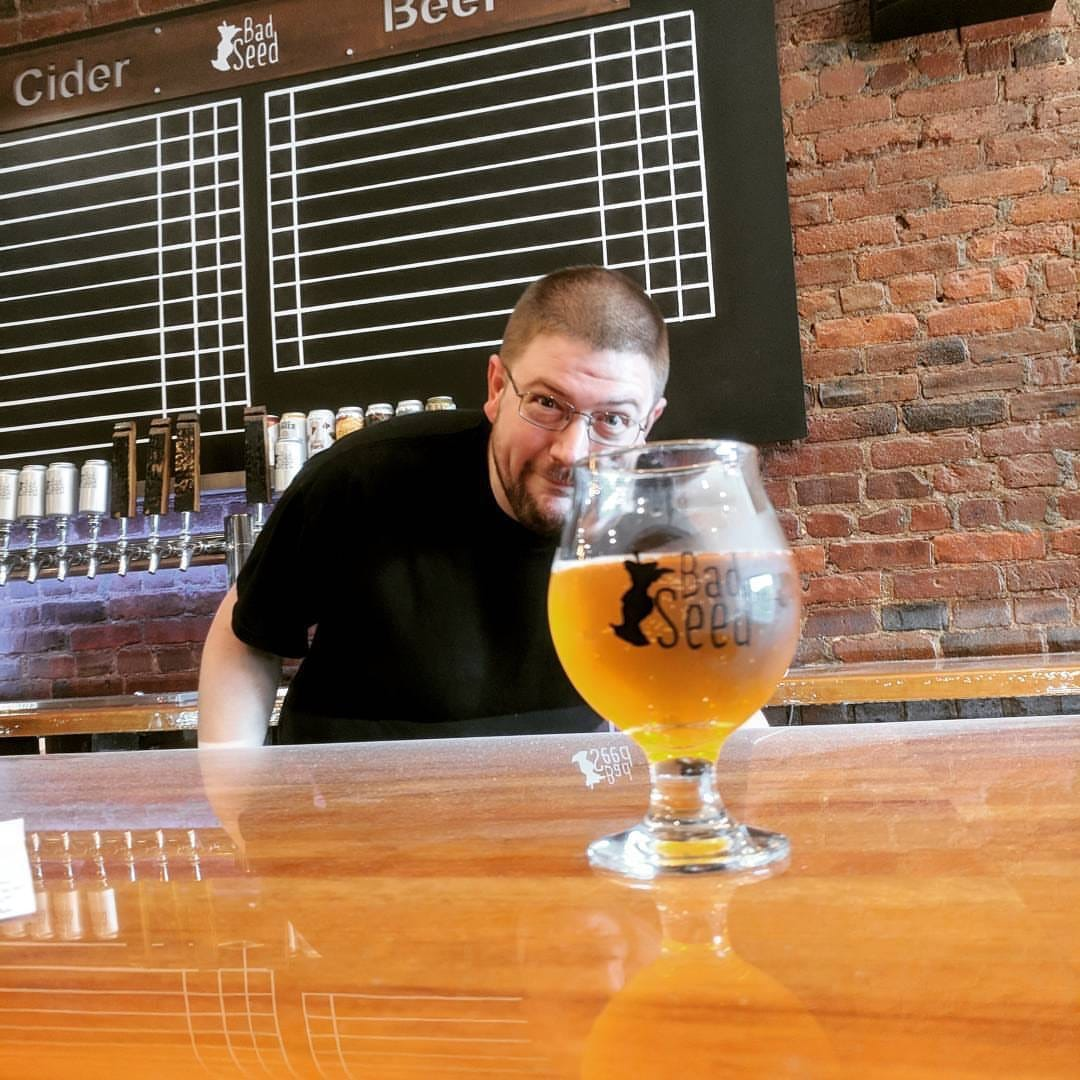 Bad Seed Co-owner Devin Britton standing behind the bar with full glass of cider on the counter