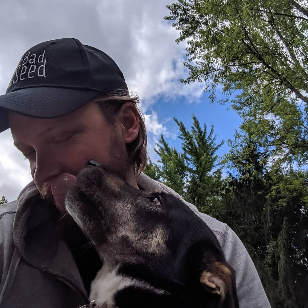 Bad Seed co-owner Bram Kincheloe wearing a Bad Seed hat with dog licking his face