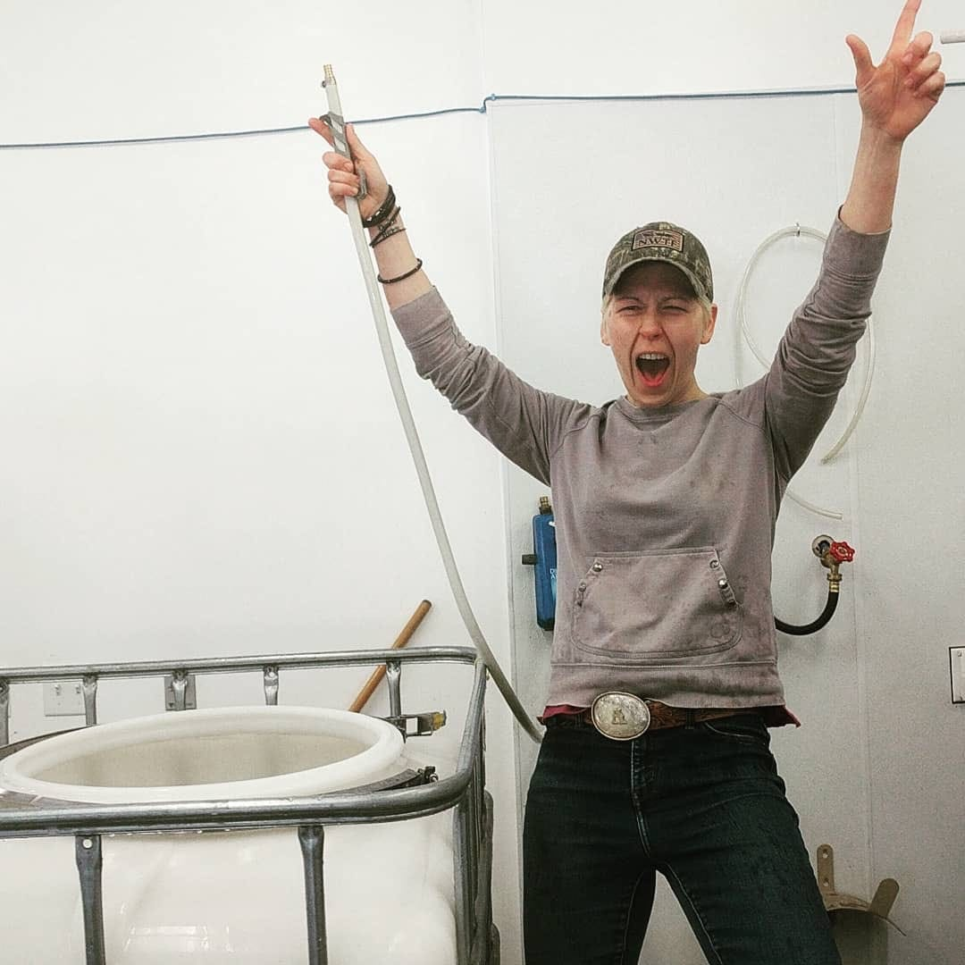Bad Seed team member Kortney Wilklow holding a hose with hands raised in the air