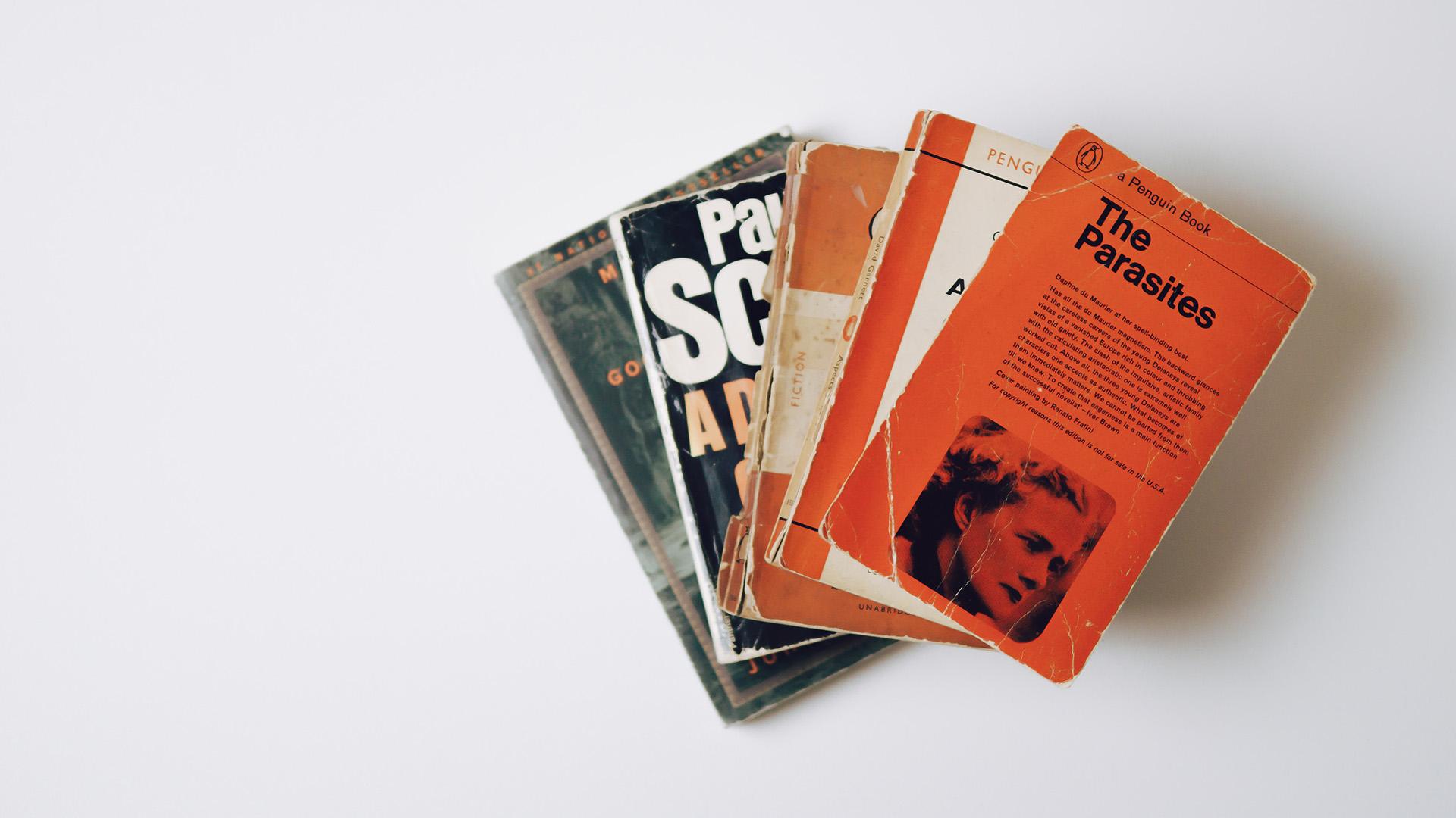 Alte, gestapelte Bücher auf weißem Hintergrund. Symbolbild für Redesign.