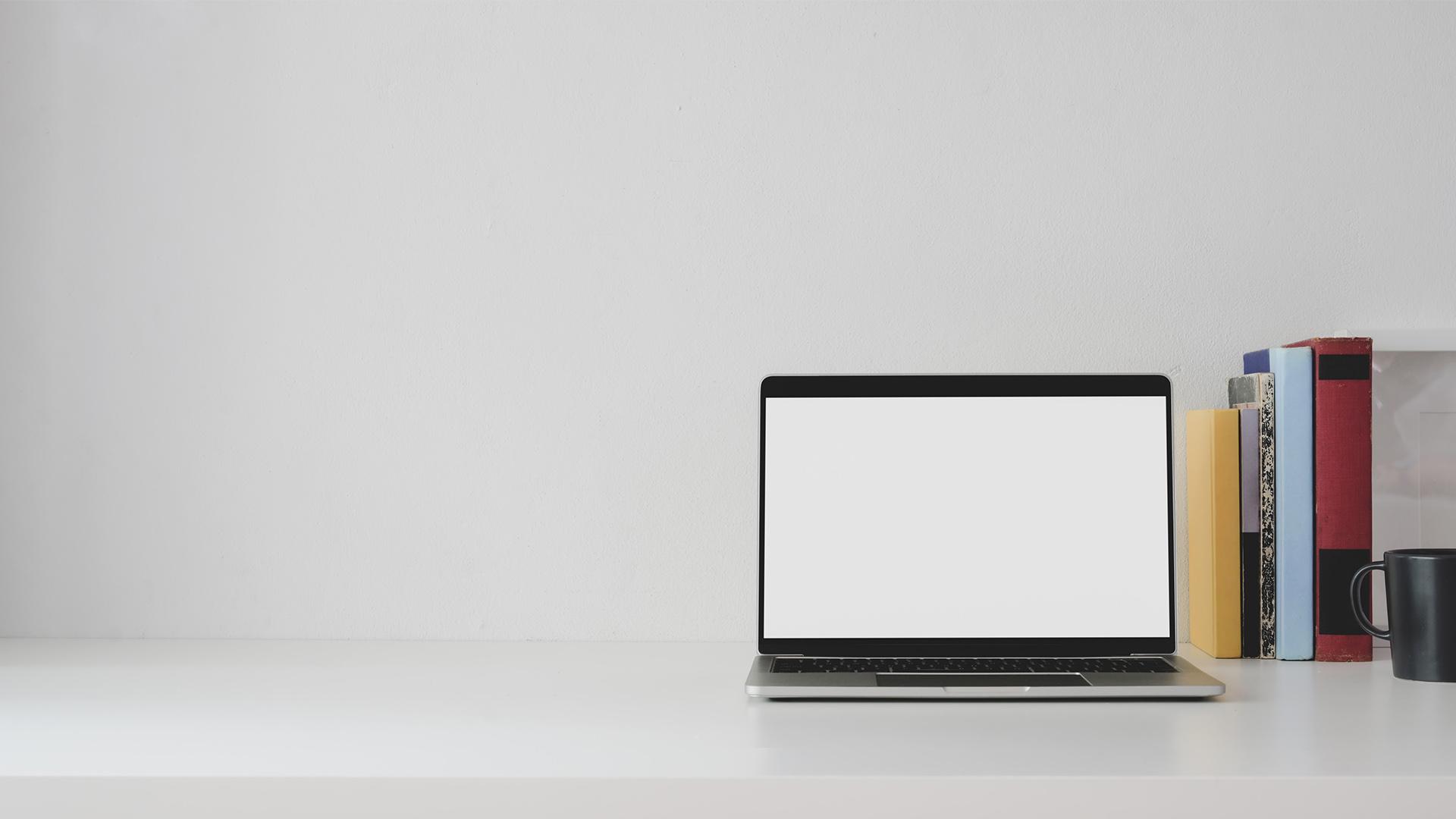Laptop auf Schreibtisch mit leerem, weißen Bildschirm. Symbolbild für Corporate Identity.