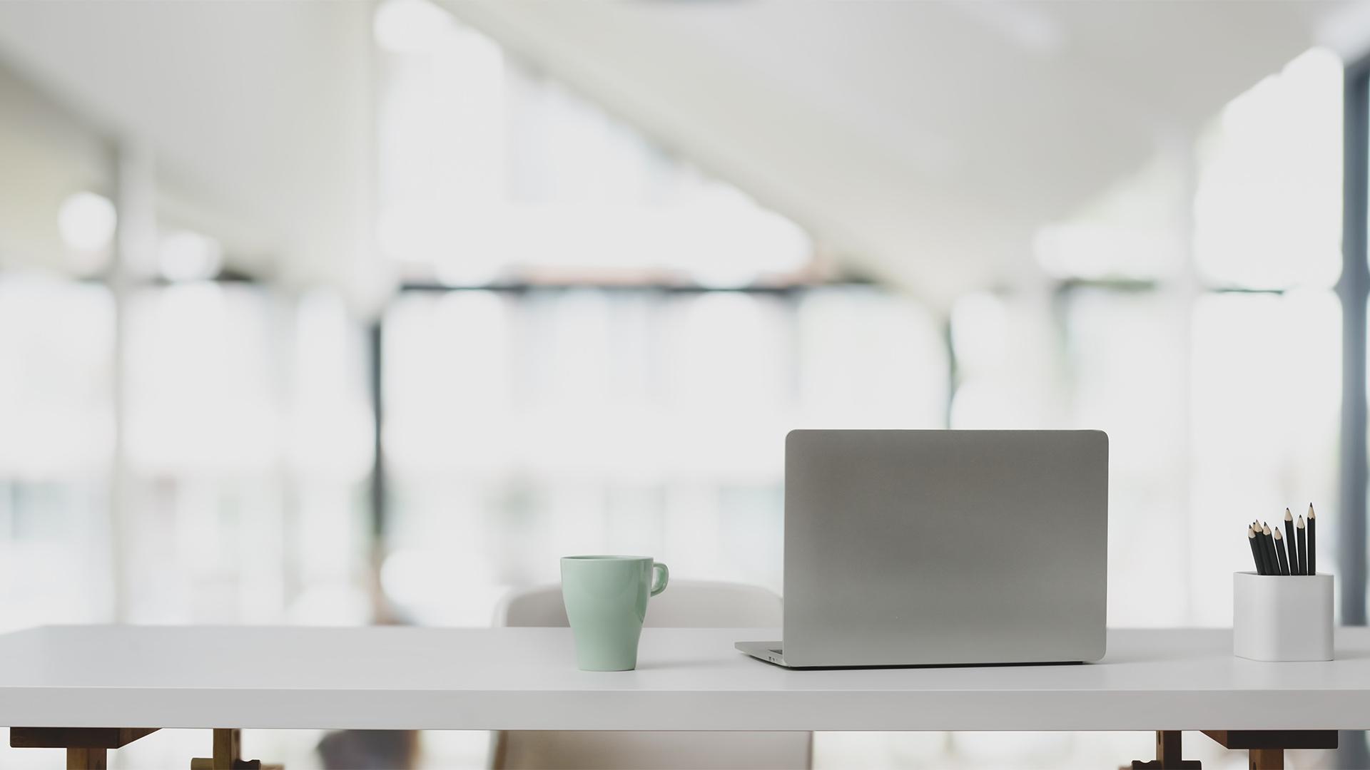Laptop auf Stehtisch vor weißer Büroraumkulisse. Symbolbild für Corporate Design.