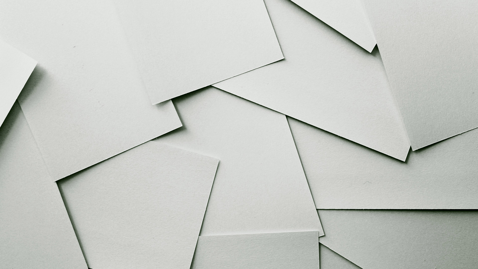 Leere, über den Tisch verteilte, weiße DINA4 Blätter. Symbolbild für Printdesign.