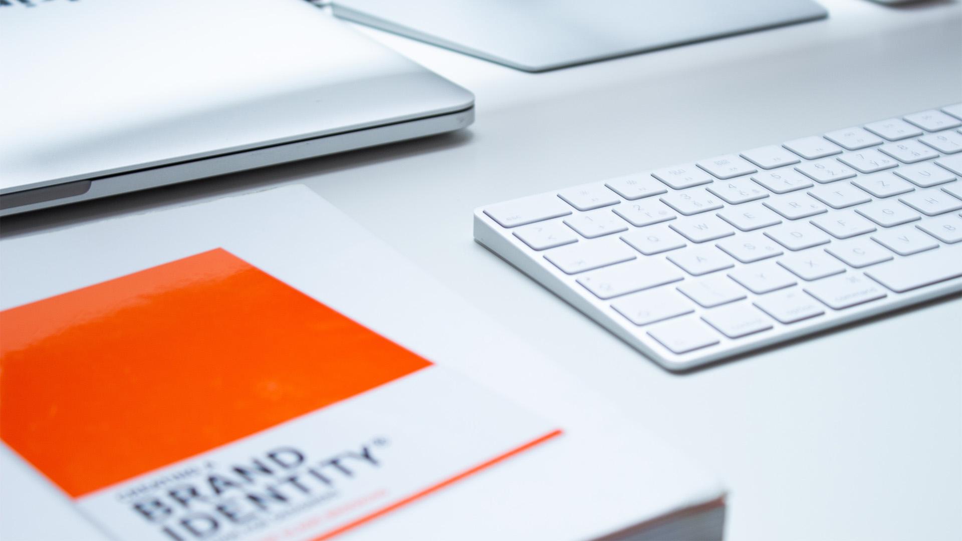 Schreibtisch mit Tastatur und Nachschlagewerk über Branding. Symbolbild für Branding.