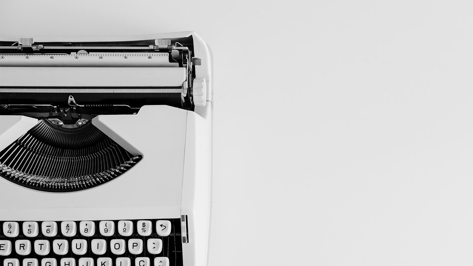Alte, weiße Schreibmaschine auf weißem Hintergrund als Symbolbild für Redesign.