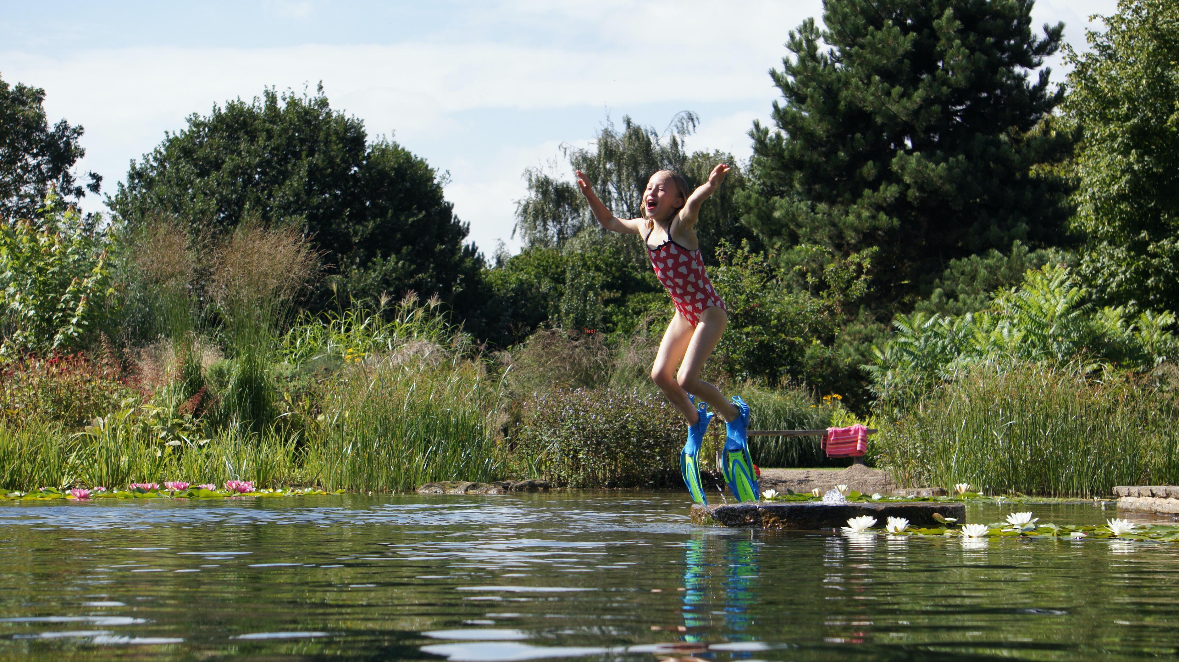 girl jumping into natural pool