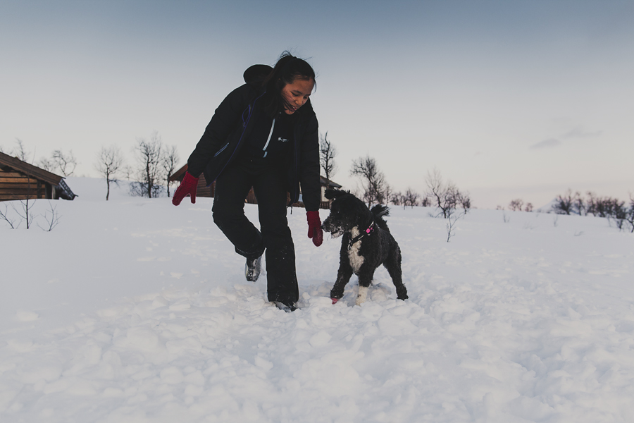 Girl and dog playing in the snow