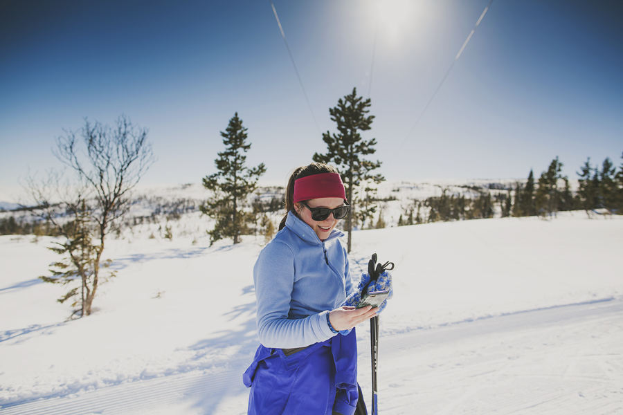 Girl wearing blue skiing and looking at her phone