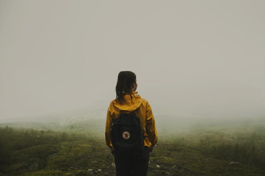 Girl with Fjellreven backpack standing in the fog