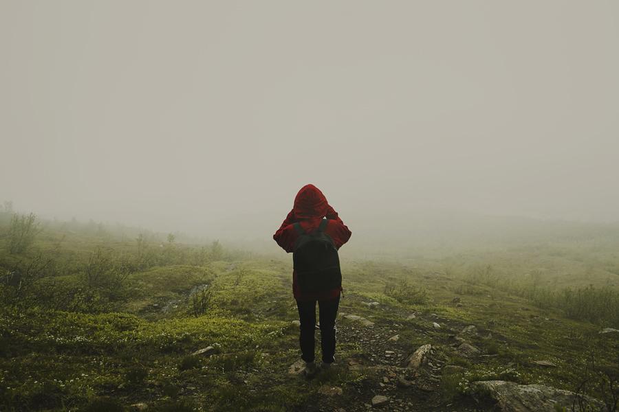 Girl in red walking in fog