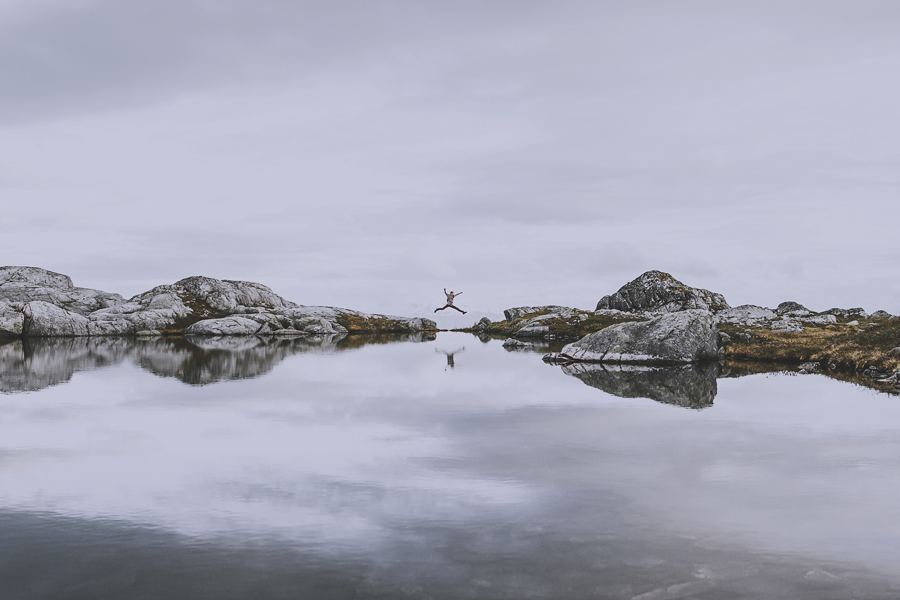 Girl jumping reflected in the water