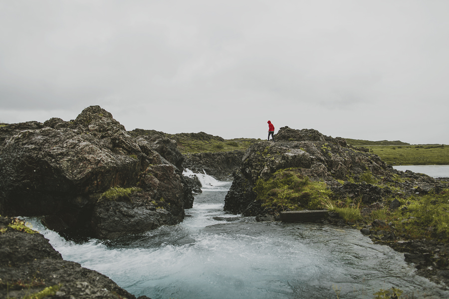 Girl in a red jacket walking by the river