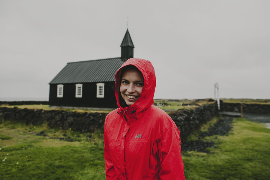 Girl in a red jacket in front of a black church