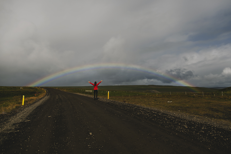 Girl standing under a rainbow