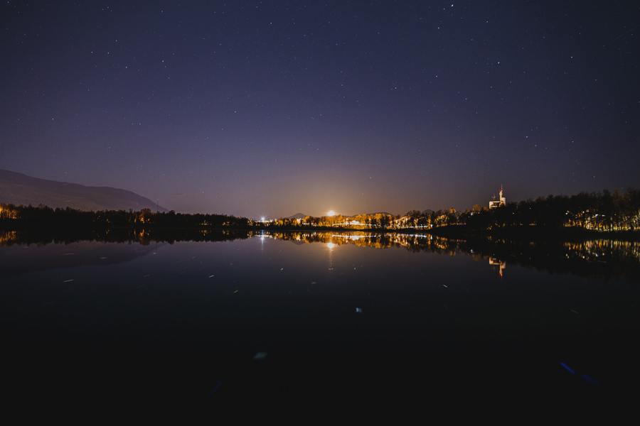 City reflected in a lake at night time