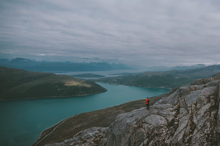 Man in orange jacket looking at the fjord