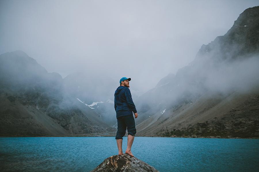 Man standing in front of Blåisvatnet covered in fog