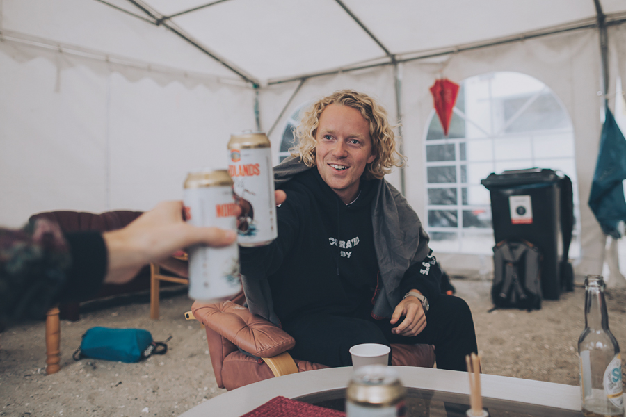 Blonde curly-haired boy with a beer