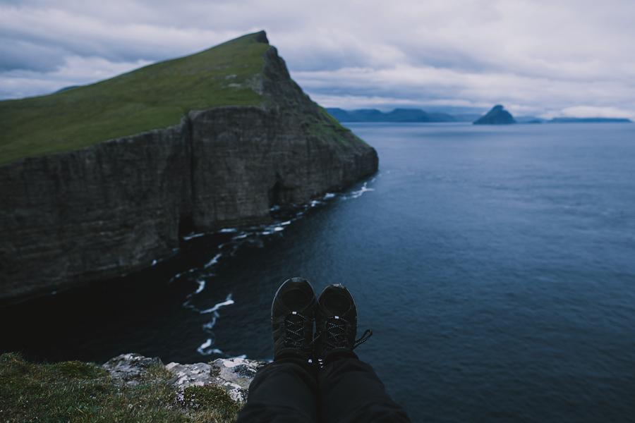 Feet dangling off the cliff in Faroe Islands