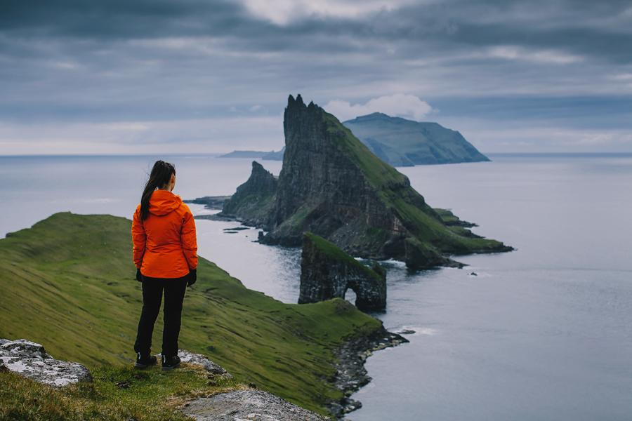 Girl in orange jacket looking down at Drangarnir in Faroe Islands